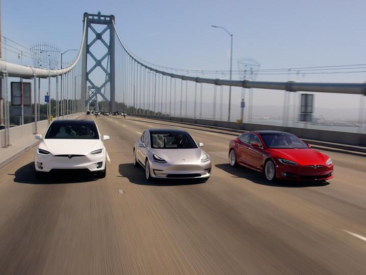 white Model X, grey Model 3, red Model S driving on a bridge
