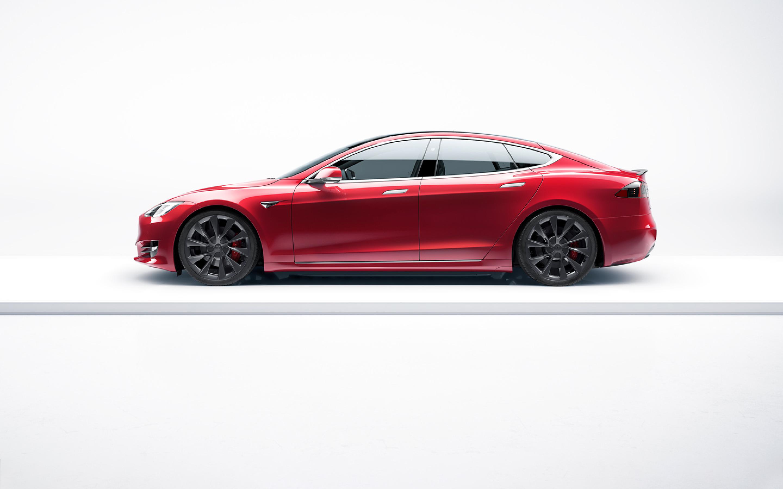 Pogled s strani na rdeči Model S z belim ozadjem