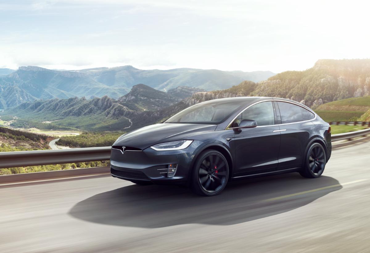 Model X בצבע אפור בנסיעה על כביש ההר